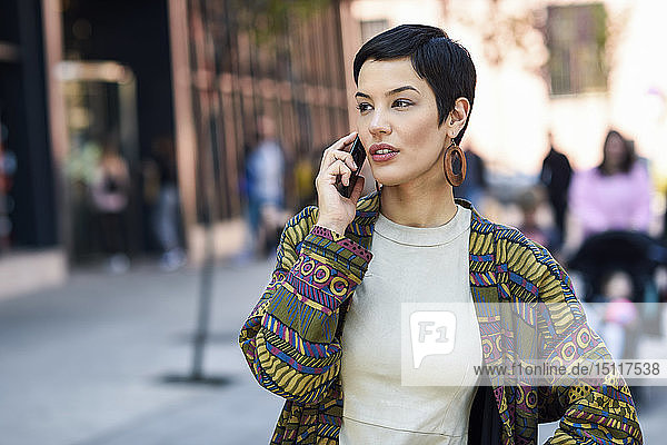 Smiling fashionable young woman on cell phone in the city