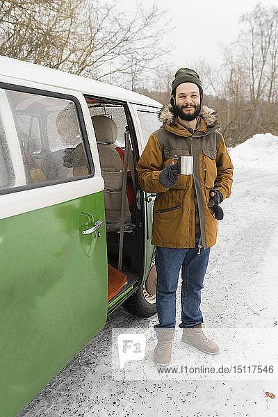 Porträt eines lächelnden Mannes mit Elektro-Van in Winterlandschaft  Kuopio  Finnland