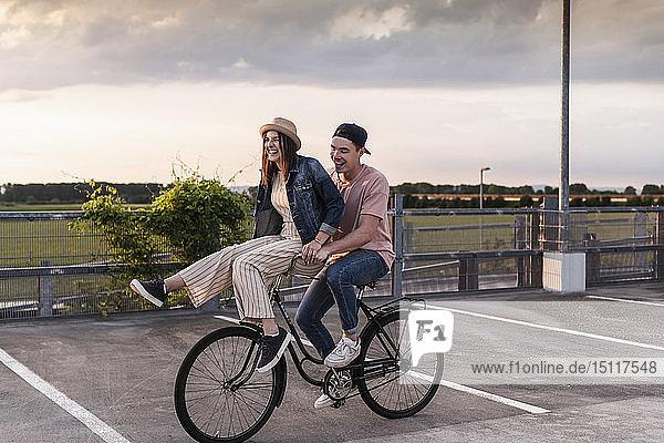 Glückliches junges Paar zusammen auf einem Fahrrad auf dem Parkdeck