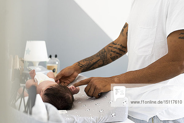 Newborn baby grabbing father's finger on changing table Newborn baby grabbing father's finger on changing table