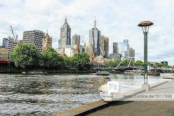 Mann sitzt am Fluss Yarra und schaut auf Wolkenkratzer in Melbourne  Victoria  Australien