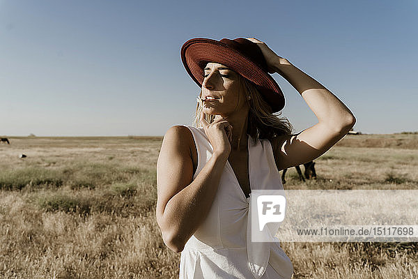 Portrait of female traveller with straw hat and flower in the mouth