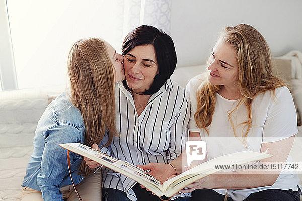 Aufgewachsene Töchter besuchen ihre Mutter und sehen sich ein Fotoalbum an