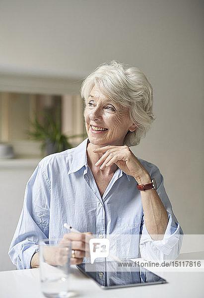 Porträt einer lächelnden reifen Frau mit digitalem Tablett am Schreibtisch