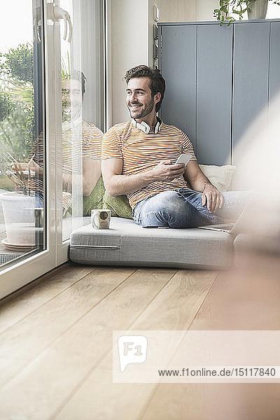 Junger Mann sitzt auf Matratze und benutzt ein Smartphone mit Kopfhörern um den Hals