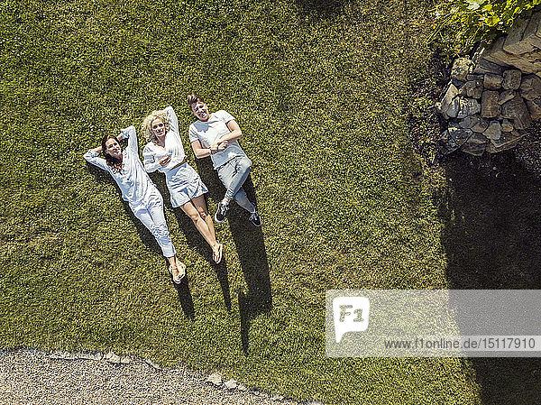 Freunde entspannen sich im Sommer auf dem Rasen
