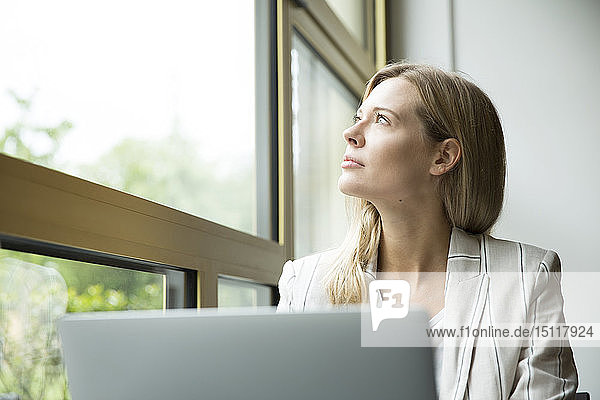 Geschäftsfrau  die aus dem Fenster schaut