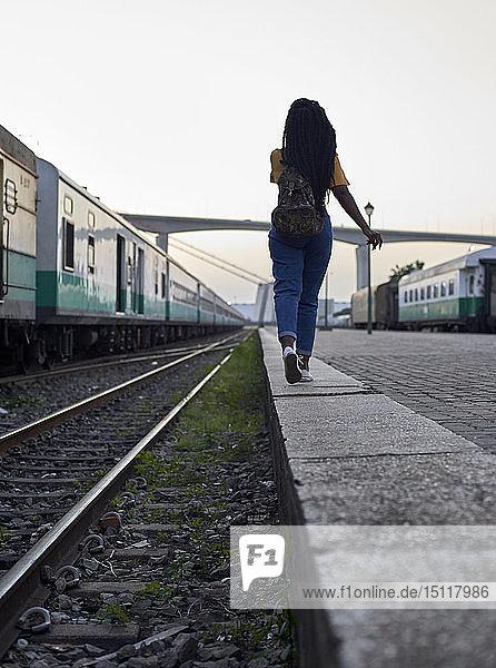 Rückansicht einer jungen Frau  die am Rande des Bahngleises am Bahnhof geht
