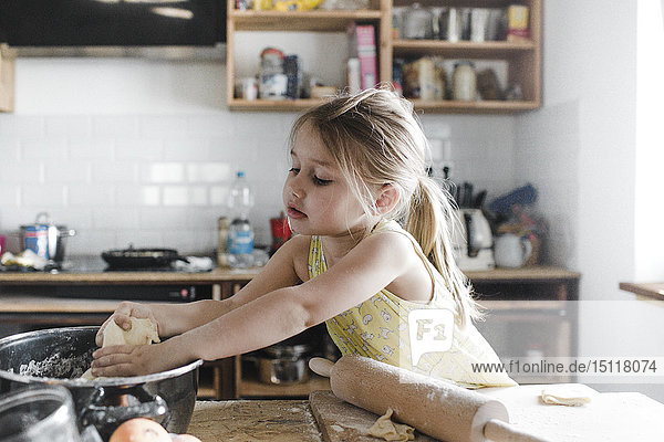 Little girl rolling out dough in the kitchen