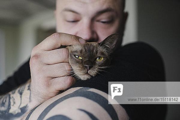 Close-up of tattooed man cuddling Burmese cat