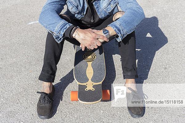 Tätowierter junger Mann auf Longboard sitzend  Teilansicht
