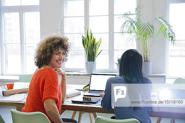 Smiling woman with colleague in modern office with video projector on table