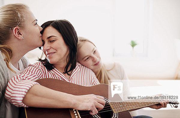 Reife Frau mit zwei liebevollen Töchtern  die zu Hause Gitarre spielen