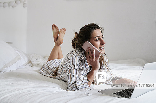Young woman lying in bed  using laptop  talking on the phone