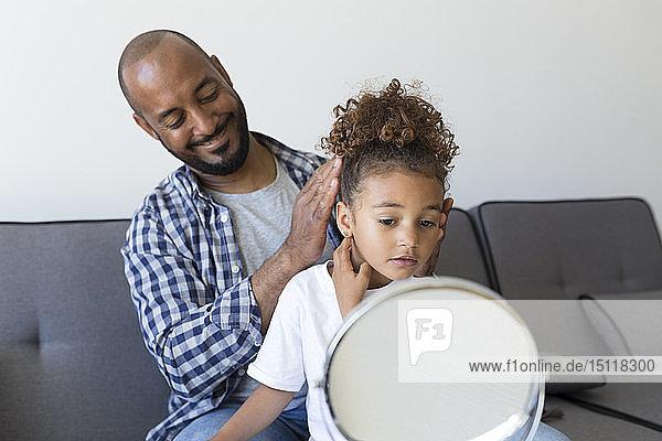 Vater frisiert zu Hause die Tochter auf der Couch