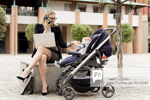 Young businesswoman with baby boy in stroller working outdoors