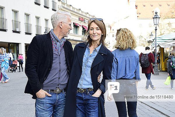 Ein erwachsenes Paar geht in der Stadt spazieren  der Mann kümmert sich um eine andere Frau
