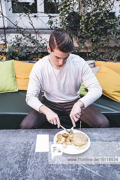 Young man sitting on couch in a restaurant having a vegan burger for lunch