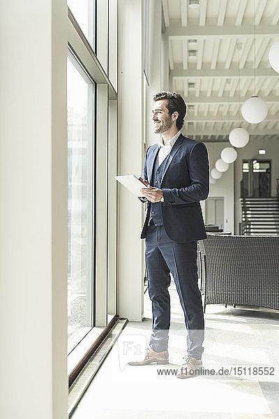 Junger Geschäftsmann steht im Bürogebäude  benutzt digitales Tablet und schaut aus dem Fenster