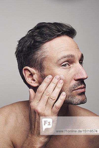 Mann,  der sein Gesicht eincremt