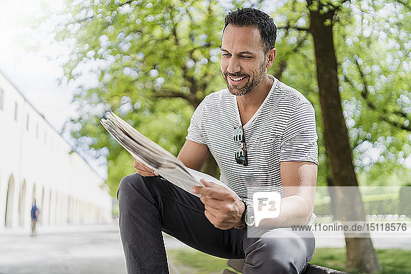 Smiling man sitting on park bench reading newspaper