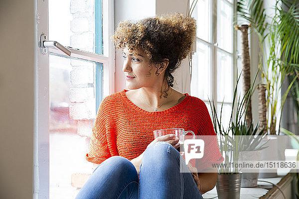 Frau mit einem Kaffee  die im Büro aus dem Fenster schaut