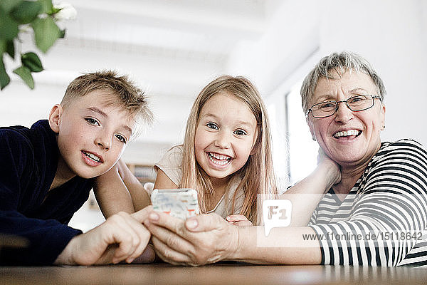 Porträt der glücklichen Grossmutter und Enkelkinder mit Handy zu Hause