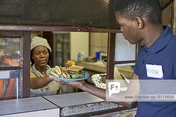 Junger Kellner  der das gelieferte Essen aus der Restaurantküche entgegennimmt  Südafrika