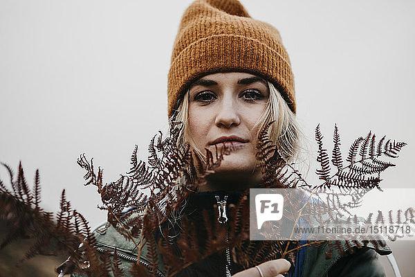 UK  Scotland  Highland  portrait of young woman holding fern