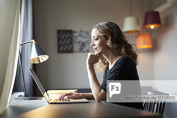 Frau benutzt Laptop am Tisch zu Hause
