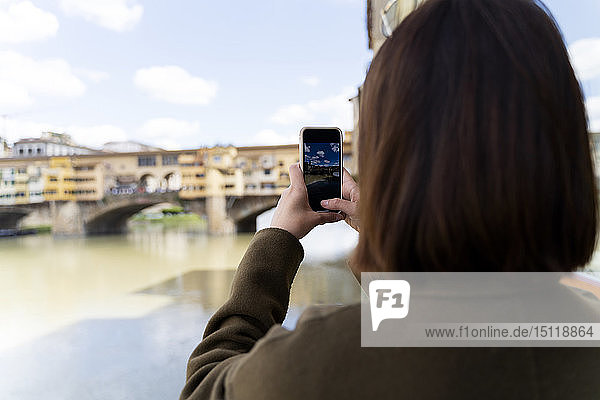 Italy  Florence  young tourist woman taking a cell phone picture at Ponte Vecchio