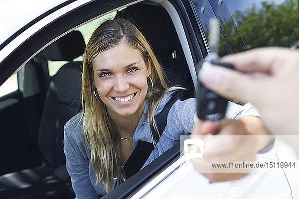 Porträt einer lächelnden jungen Frau  die in die Kamera schaut  während sie die Autoschlüssel in der Hand hält und sie jemandem durch das Fenster gibt