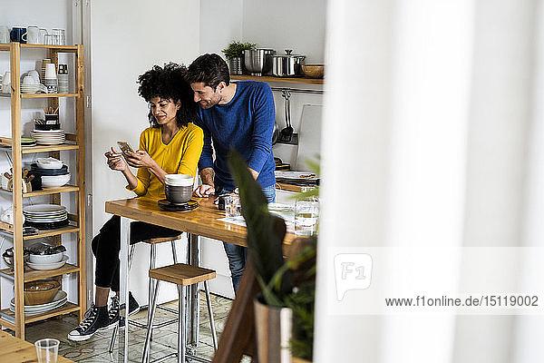 Ehepaar in der Küche zu Hause teilt sich ein Mobiltelefon