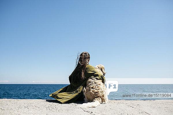 Rückenansicht einer Frau  die neben ihrem Labrador Retriever am Kai sitzt und auf den Horizont schaut