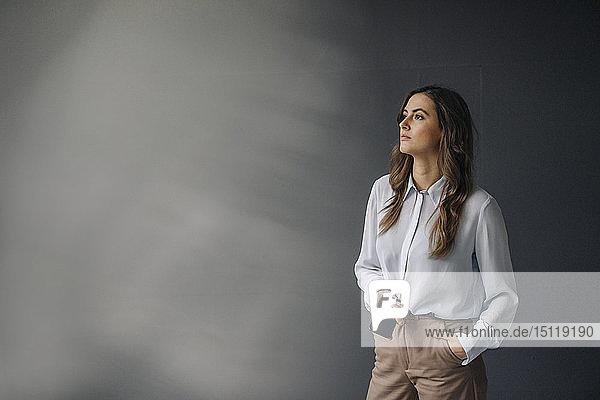 Porträt einer seriösen jungen Geschäftsfrau mit seitlich schauendem Handy