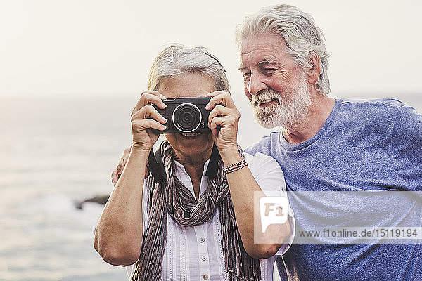 Travelling senior couple  taking pictures at the sea
