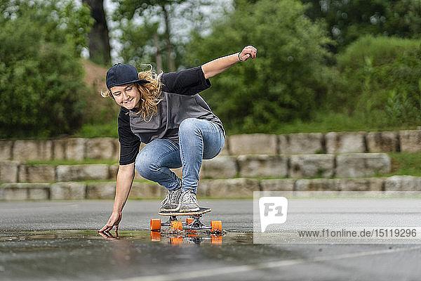 Junge Frau balanciert auf Skateboard