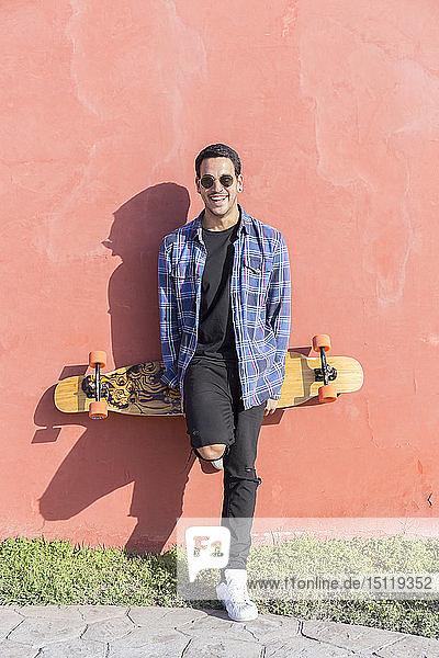 Porträt eines lachenden jungen Mannes mit Longboard vor rosa Wand stehend