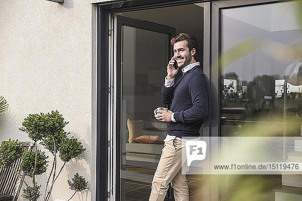 Junger Mann lehnt in Tür seines Hauses  hält Tasse Kaffee in der Hand  benutzt Smartphone