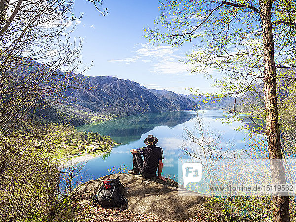 Italy  Lombardy  spring at Lake Idro  hiker sitting on observation point