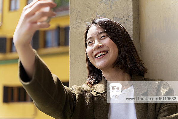 Italy  Florence  happy young woman taking a selfie in the city