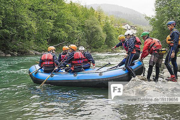Gruppe von Personen,  die mit einem Schlauchboot auf einem Fluss eine Rafting-Tour beginnen