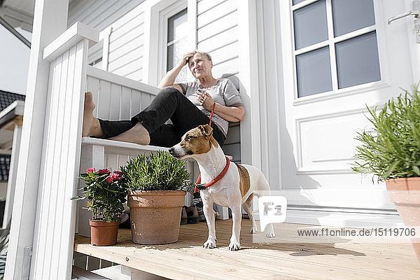 Entspannte ältere Frau sitzt mit ihrem Hund auf der Veranda
