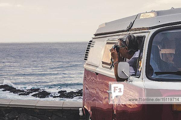 Ältere Frau sitzt in einem Oldtimer-Van und fotografiert das Meer