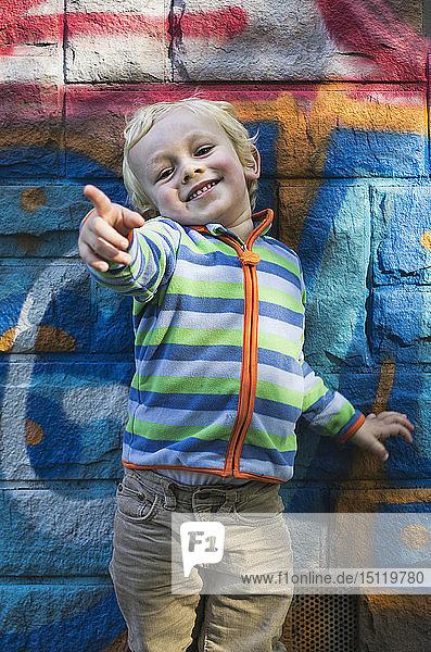 Porträt eines lächelnden kleinen Jungen  der vor einer bunten Wand steht und auf etwas zeigt