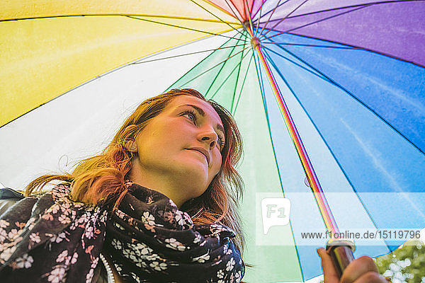 Junge Frau unter buntem Regenschirm