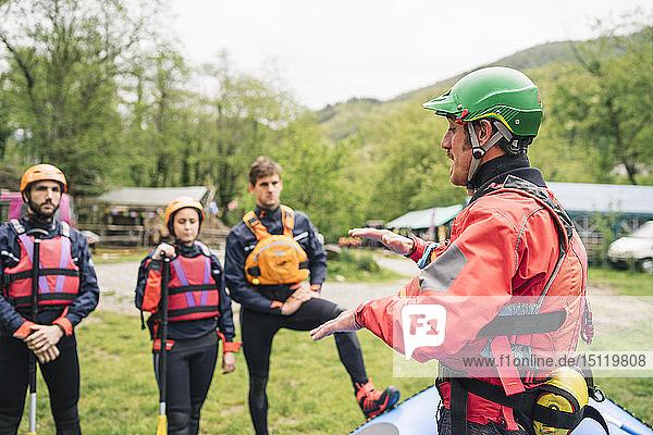 Ausbilder im Gespräch mit einer Gruppe von Freunden bei einem Rafting-Kurs