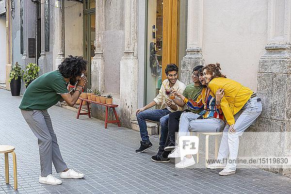 Mann macht ein Foto von Freunden  die in der Stadt etwas trinken