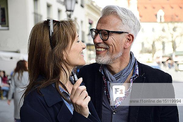 Reifere Paare gehen in der Stadt spazieren  Frau raucht elektronische Zigarette
