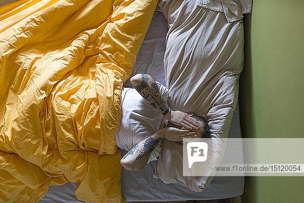 Tätowierter Mann im Bett liegend  Hände auf den Augen